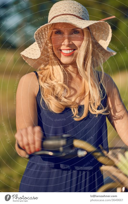 Attractive blond woman with lovely friendly smile standing outdoors with her bicycle in the spring sunshine wearing a broad brimmed straw sunhat attractive