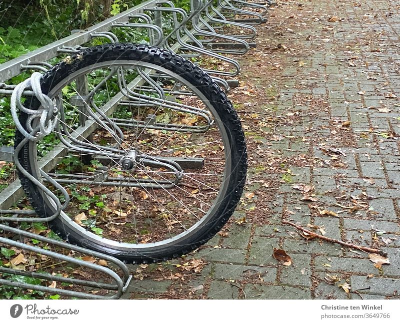 Only the front wheel of the bicycle is still properly chained in the bicycle stand. Bicycle theft Front wheel tethered Chained up Bicycle rack stolen dismounted