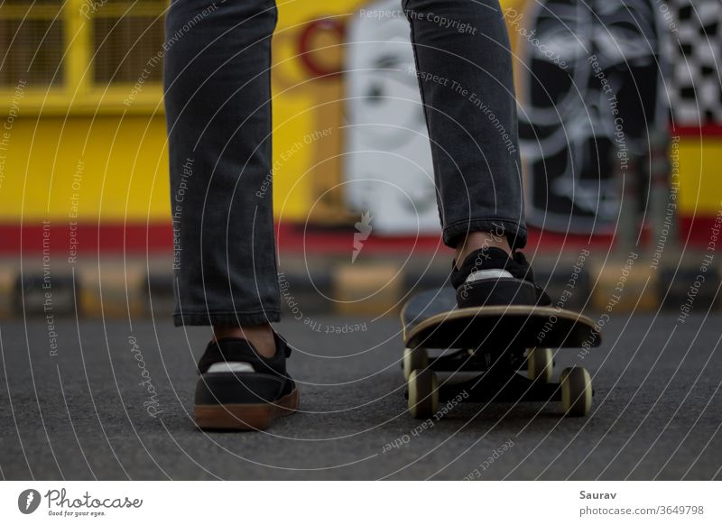 A young man standing while keeping his foot on a Skateboard. skateboarding summer new normal sports leisure lifestyle sneaker outdoors young adult skating