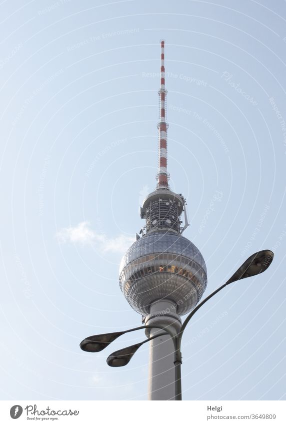 necklace - three-armed lamp stands decoratively in front of the Berlin television tower, the sky is blue with a little cloud Television tower Lamp streetlamp