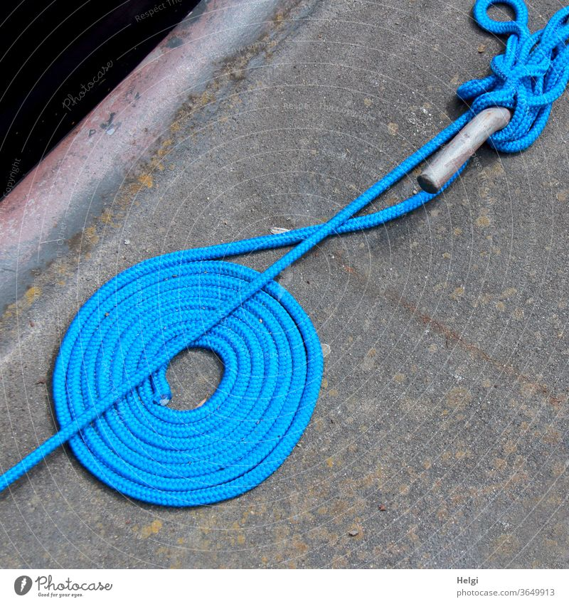some order must be - blue fastening rope lies neatly rolled up and untidily wrapped around a pole on a quay wall Rope Dew Fastening coiled Wrapped around Rod