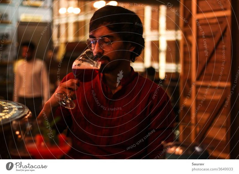 Young Man wearing red shirt while drinking Red Wine from a goblet at a bar indoors with colorful lights all around him. lifestyle celebration alcohol wine