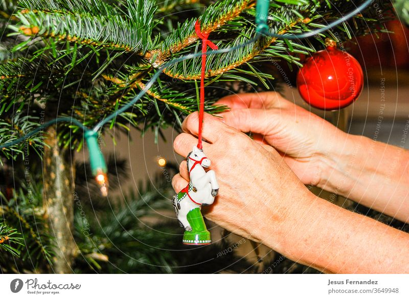 Woman hangs christmas  from a tree at home christmas tree figures hands holidays indoors ornaments seasonal spheres stars tradition