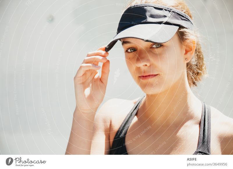 Portrait of a beautiful young sporty woman with visor cap in a warm day model fashion portrait face posing running isolated happy smiling runner wall gorgeous