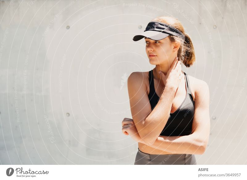 Portrait of a beautiful young sporty woman with visor cap in a hot day model fashion portrait posing running isolated happy smiling runner wall athlete gorgeous
