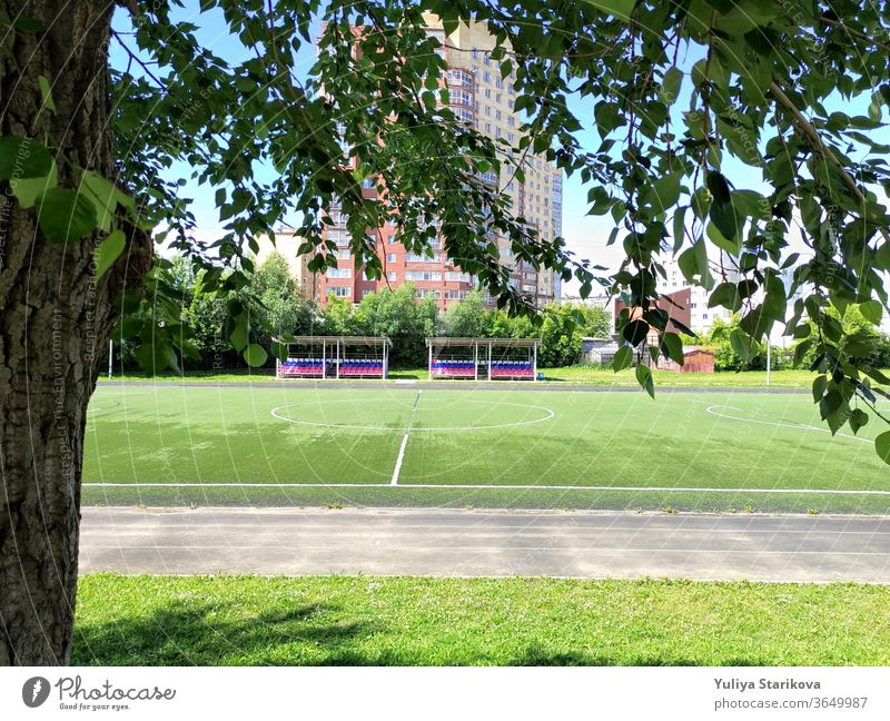 Empty green soccer field near a school and the apartment house in Russia. Stadium and football field with empty spectator seats. Keeping fit and exercising outdoor. Urban view in a frame of leaves.