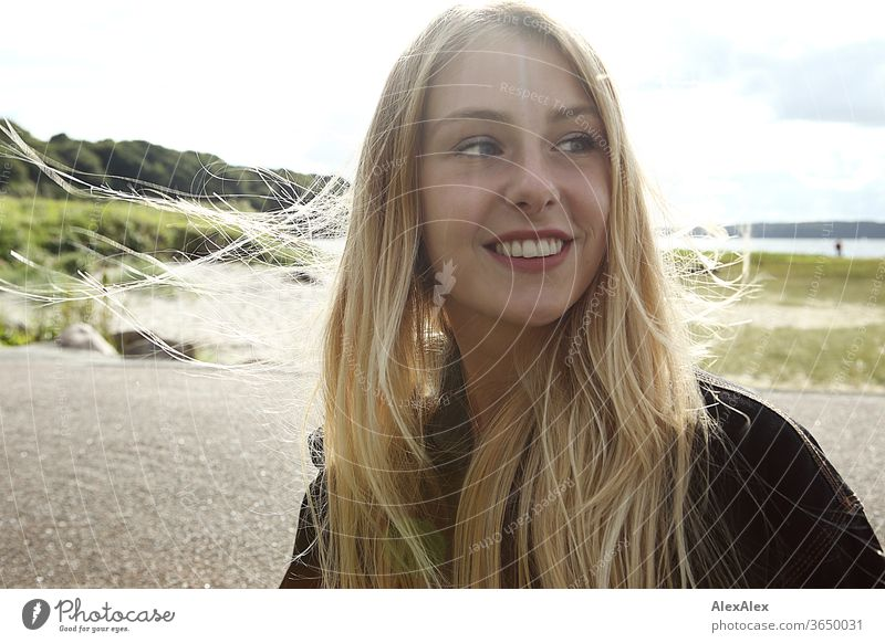 Backlit portrait of a young, blond, smiling woman at the sea Woman Young woman Blonde already Slim Long-haired windy Esthetic Summer Trip Beautiful weather