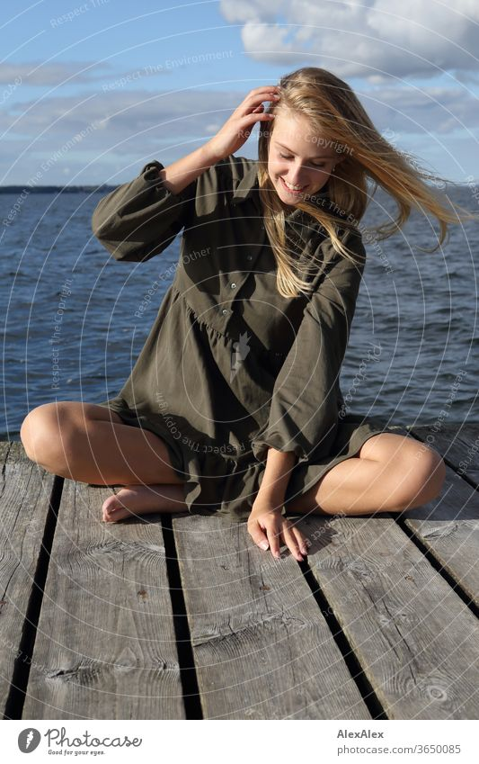 Full body portrait of a young, blond, barefoot woman on a wooden jetty in the sea Woman Young woman Blonde already Slim Long-haired windy Esthetic Summer Trip