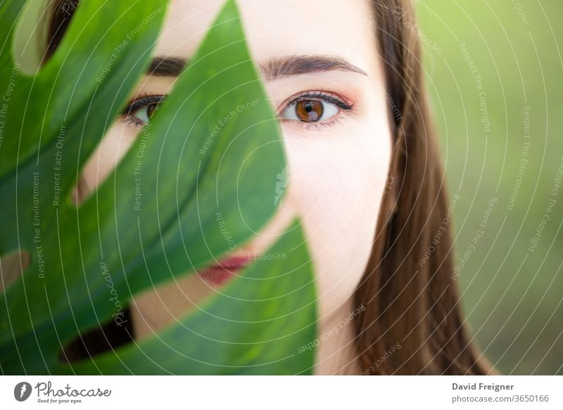 Beautiful natural young woman closeup behind big monstera leaf with green background in the woods. skin beautiful girl beauty health model female nature