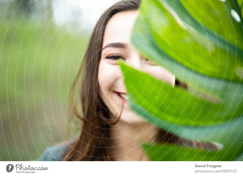 Beautiful natural young woman closeup behind big monstera leaf with green background in the woods. smile face attractive clean cute organic purity pure eyes