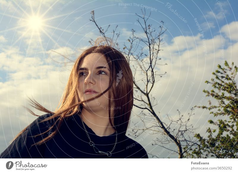 Girl is standing outdoors with blue sky, tree and sun portrait nature Person day beauty modern attractive girl real real person hair copy space teenager