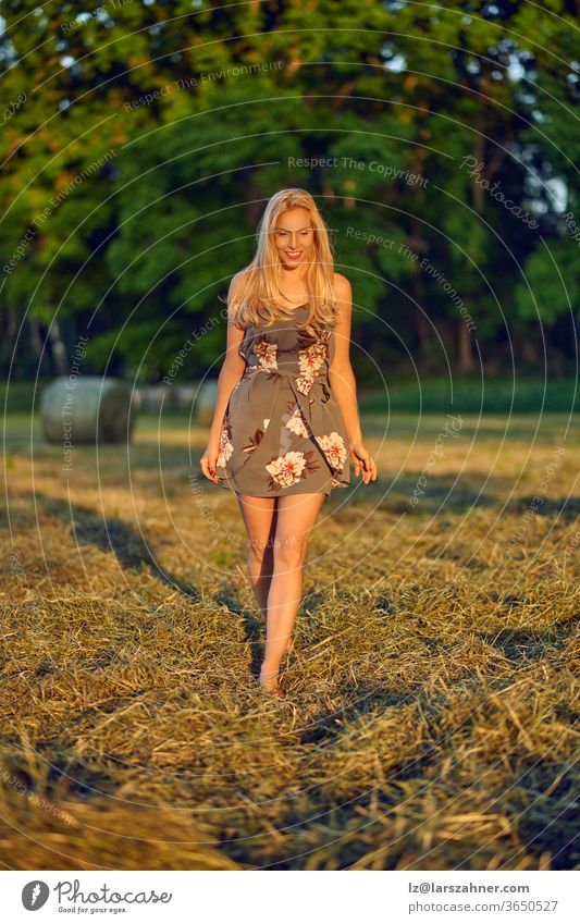 Attractive slender blond woman in a farm field walking towards the camera in a trendy summer dress in the warm glow of evening light attractive sunset