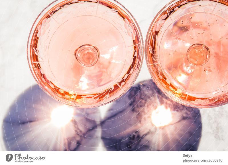 Two crystal stemmed glasses with rose wine white marble party pink drink dinner table luxury light background modern alcohol bar beautiful celebration concept