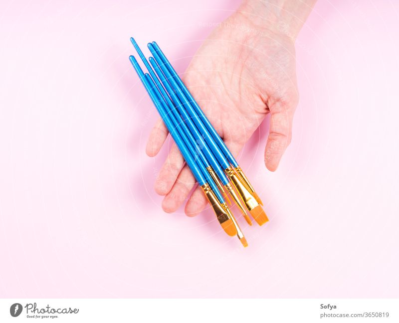 Blue paintbrushes in woman's hand on pink art art supply artist flat lay bristle painting hold different background blue class craft design acrylic equipment