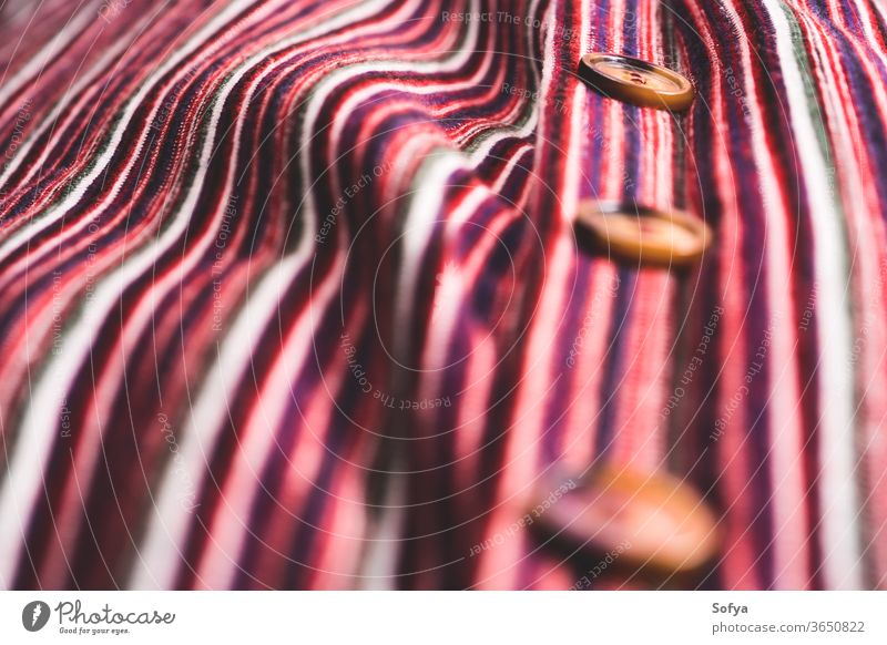 Detail of button down striped dress detail selective focus texture female fabric textile woven cotton thread color colorful red pink dark angle view fashion