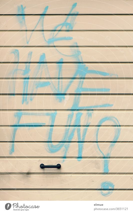 """""""WE HAVE FUN"""" is written in large light blue graffiti on a beige metal garage door above the handle we have fun Daub Graffiti Garage door Damage to property"""
