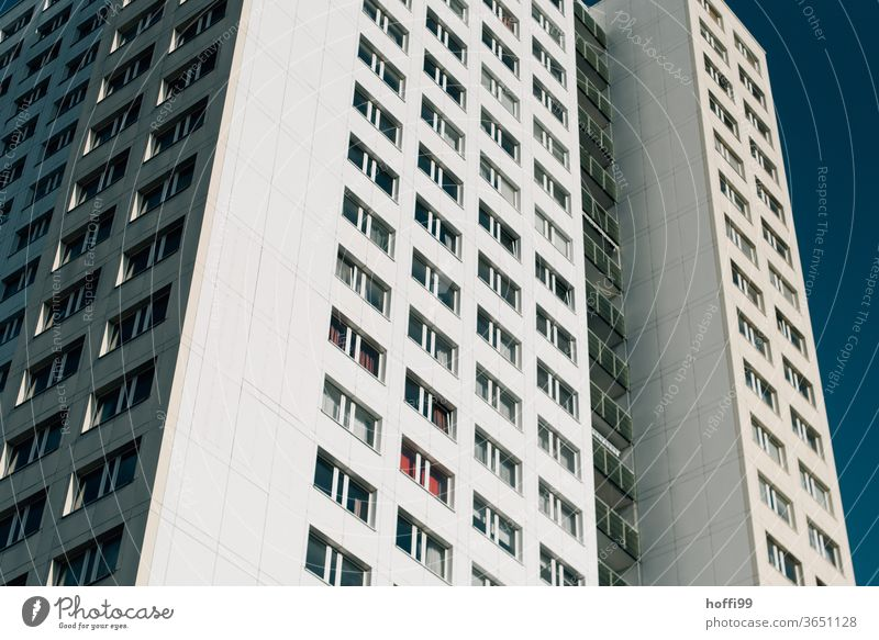 a skyscraper with many windows rises into the sky Apartment Building High-rise facade angles Wall (barrier) Line Window Symmetry Modern Facade Architecture