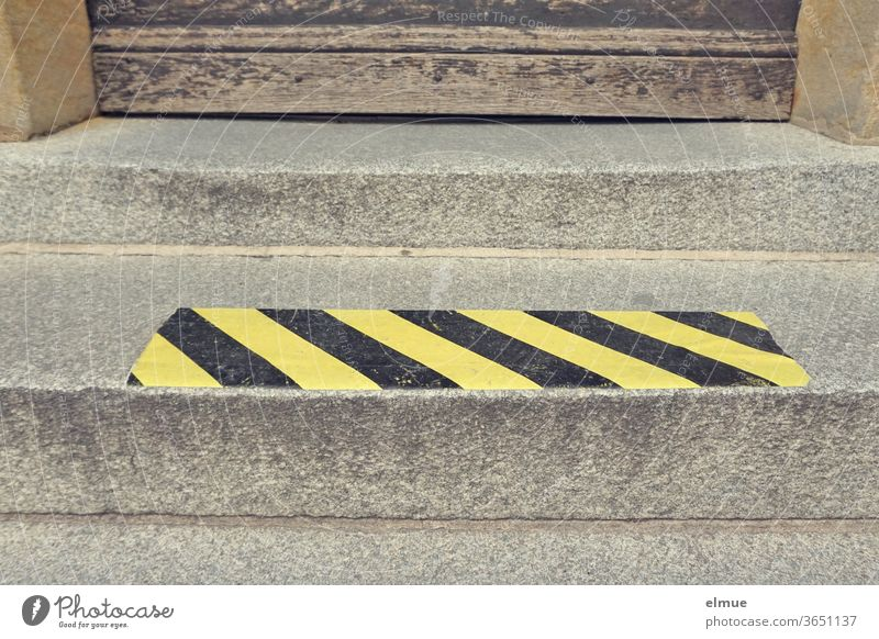 yellow-black signal strip as spacer on a stair step in front of an old wooden door gap protective measure Contact ban Protection against infection corona