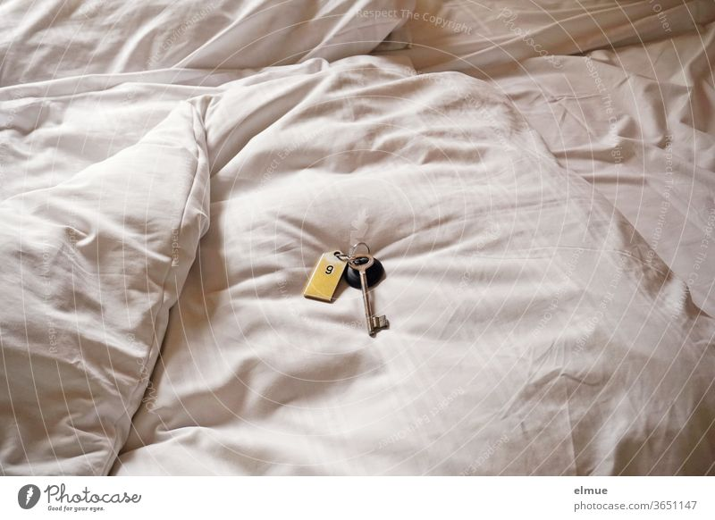 on a white covered hotel bed the old room key including the tag with the room number Hotel Hotel room Trailer overnight Bed Bedclothes Duvet Double bed White