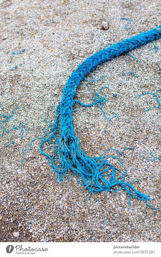 Torn blue rope Rope Dew Blue Street Asphalt Broken Lie load limit Fringe Maritime Exterior shot Harbour Colour photo Deserted fails Day Close-up