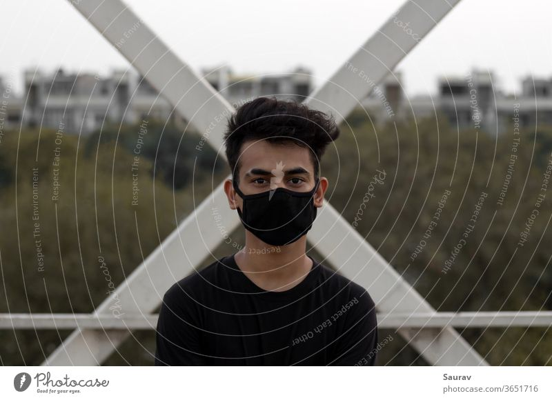 A young man wearing a protective face mask to avoid Coronavirus infection in a city. coronavirus covid 19 young adult new normal lifestyle summer portrait