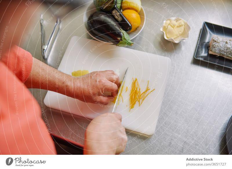 Crop unrecognizable cook peeling lemon while preparing garnish for fish zest chef prepare cut food culinary ingredient dinner menu recipe process lunch citrus