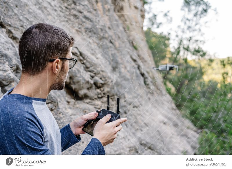 Focused man operating drone remotely control fly operate quadrocopter controller equipment unmanned flight male landscape mountain record video innovation
