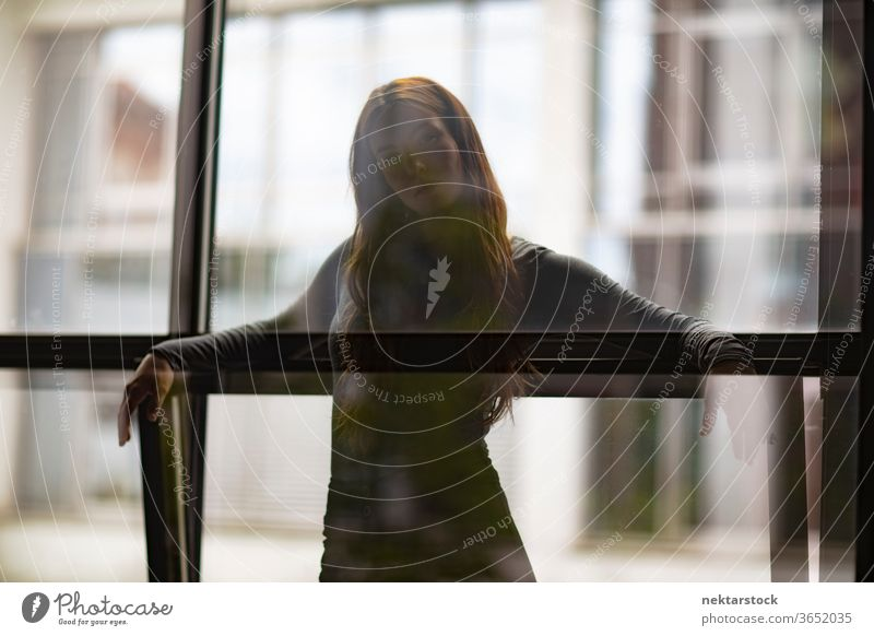 Attractive Woman Behind Window Glass Partition female one person girl young woman glass silhouette three quarter length window contemplation thought
