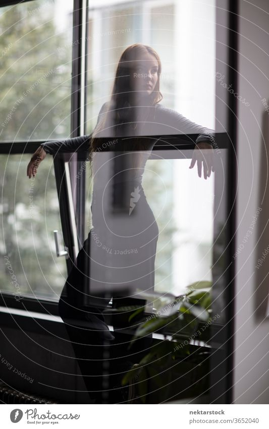 Attractive Woman Behind Glass Wall Partition female one person girl young woman glass silhouette three quarter length window contemplation thought looking away
