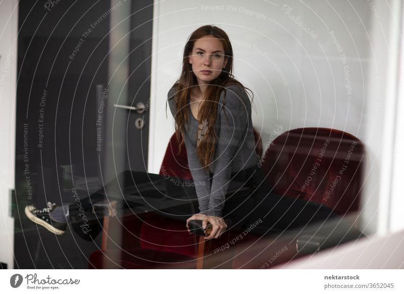 Young woman in Splits Position Across Red Velvet Armchair armchair female one person girl young woman velvet model indoors glass reflection looking at camera