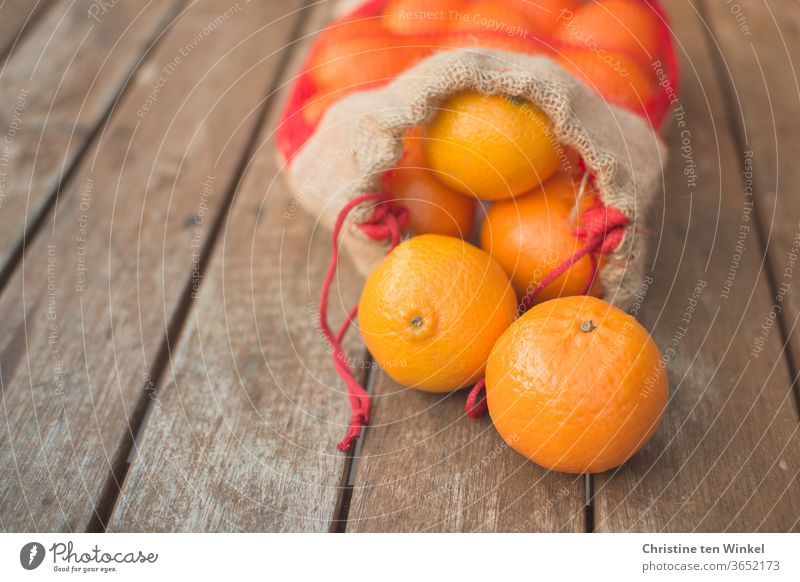 An opened bag of mandarins lies on an older wooden table. Two fruits lie in front of the bag. Close-up with shallow depth of field Citrus fruits Fresh