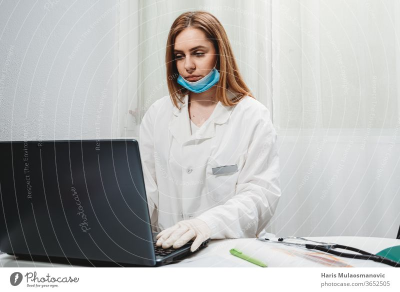 Female doctor with mask working on laptop in the doctors office teledoctor 2020 air mask black background clinic corona epidemic corona virus covid-19