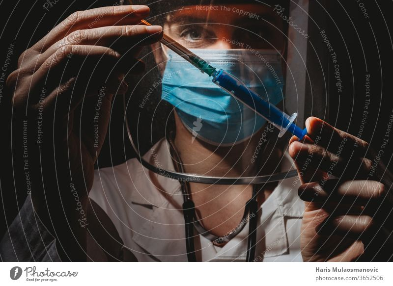 Female doctor with mask and shield holding vaccine in hands on black background 2020 air mask clinic corona epidemic corona virus coronavirus