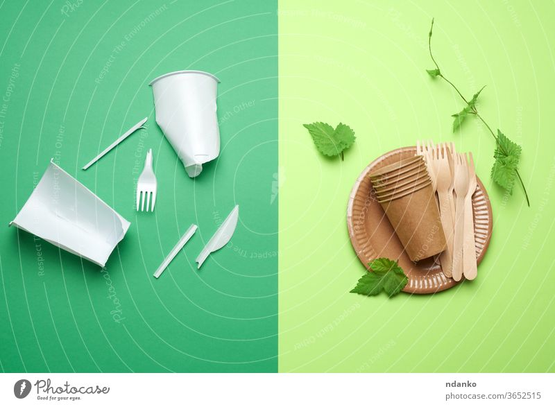 non-degradable plastic waste from disposable tableware and a set of dishes from environmental recycled materials on a green background opposition antipode trash