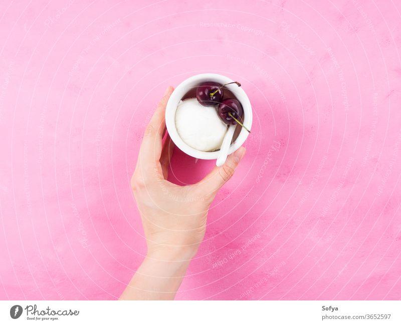 Frozen yogurt dessert in cup in female hand scoop sorbet holding gelato ice cream pink cherry minimal frozen white berries sundae sweet fruit fresh temptation