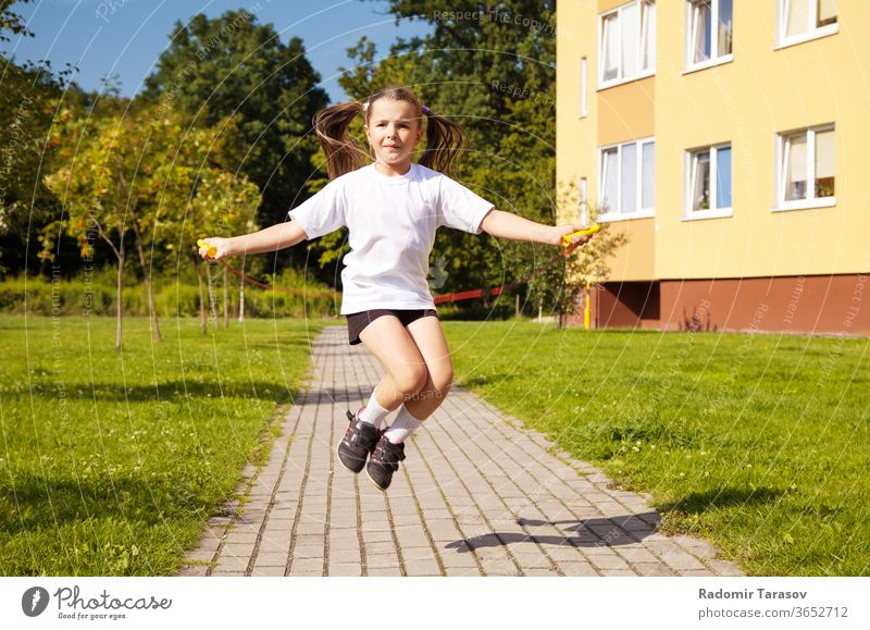 little girl jumping rope outside child cute beautiful white fun pretty cheerful lifestyle childhood play people caucasian kid joy action one beauty grass energy