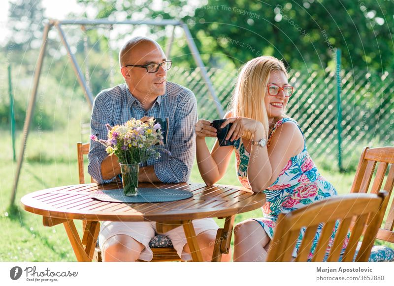 Young couple drinking coffee in the backyard in the morning adult casual caucasian cheerful communication country day enjoying evening family female garden girl