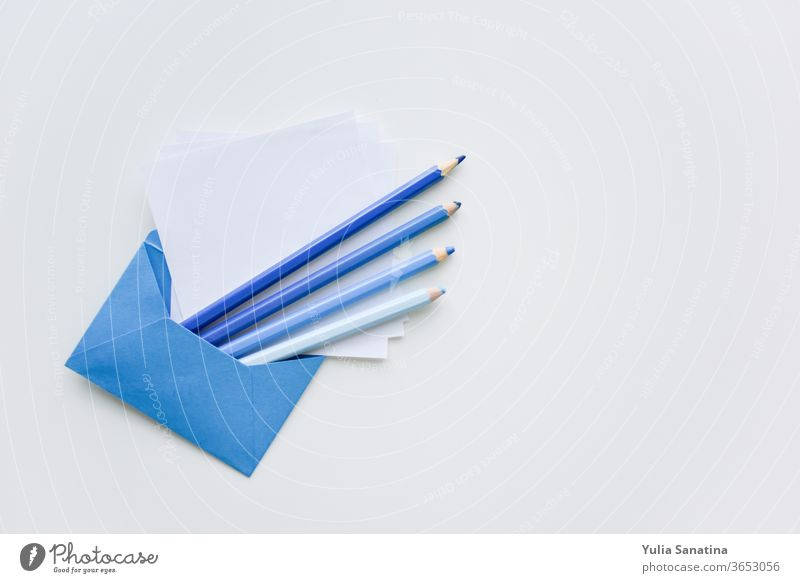 selective focus, blue pencils and white papers out of the blue envelope with copy space on top sheet background message blank letter office empty note