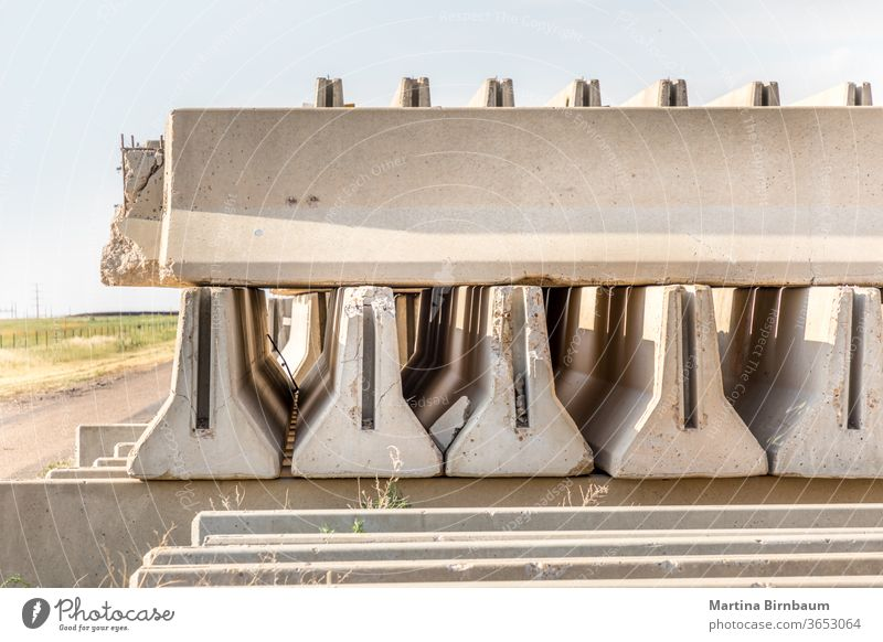 Concrete parts piled up besides a rural road besides the highway construction outside concrete block cement stone house work plant production stacked material
