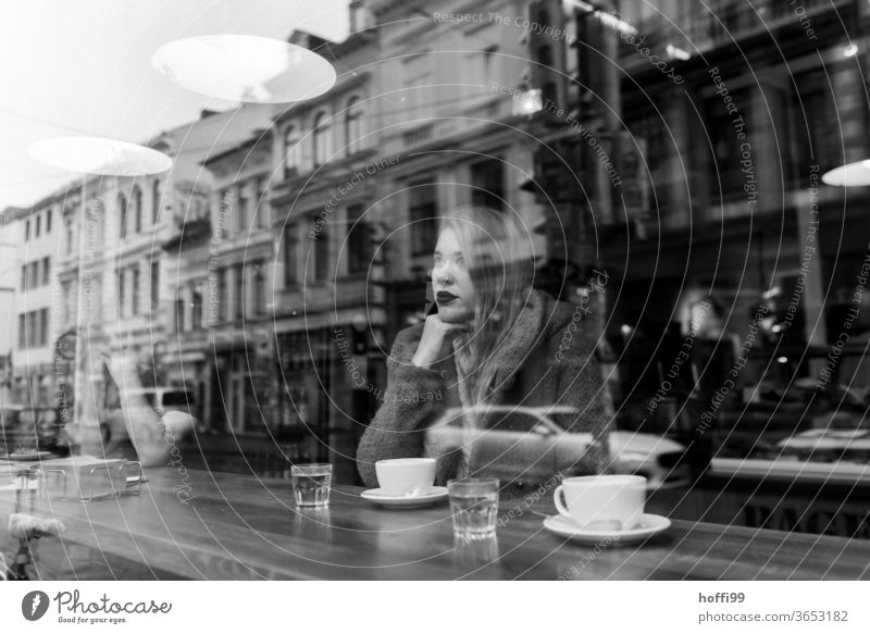 the young woman waits in the coffee shop and looks dreamily and thoughtfully out of the window Face of a woman Young woman Woman 1 portrait Youth (Young adults)