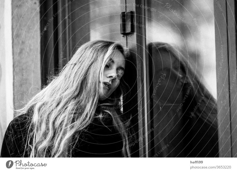 the young woman leans dreamily and melancholically against a window pane Young woman portrait Women's eyes Woman Face of a woman Youth (Young adults)