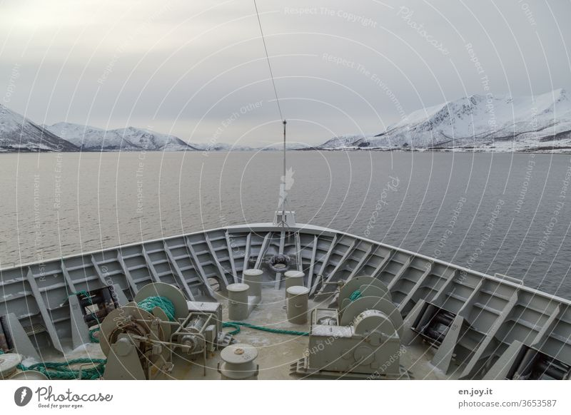 Bow of a ship with view of the Lofoten in Norway Navigation Ocean North Sea Lofotes Scandinavia Winter mountains Snow Sky Clouds Covered chill voyage vacation