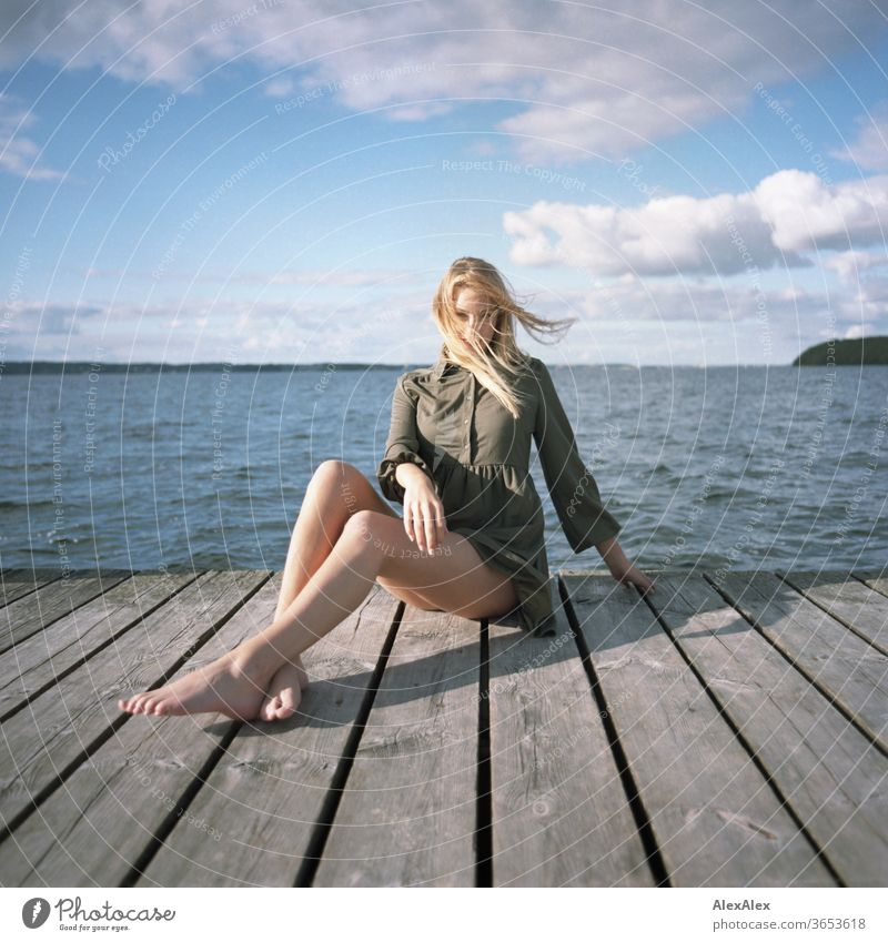 analogue full body portrait of a young, blond, barefoot woman on a wooden jetty in the sea Woman Young woman Blonde already Slim Long-haired windy Esthetic