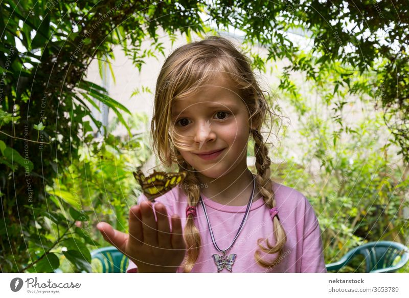 Low Angle View of a Child With Butterfly on Fingertips butterfly girl child portrait fingertips low angle view close up outdoor nature beauty in nature blond