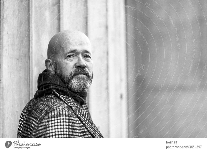 the man turns back and looks into the camera Man Facial hair Beard Coat Baldy Adults Masculine Human being portrait 1 Looking into the camera Exterior shot Face