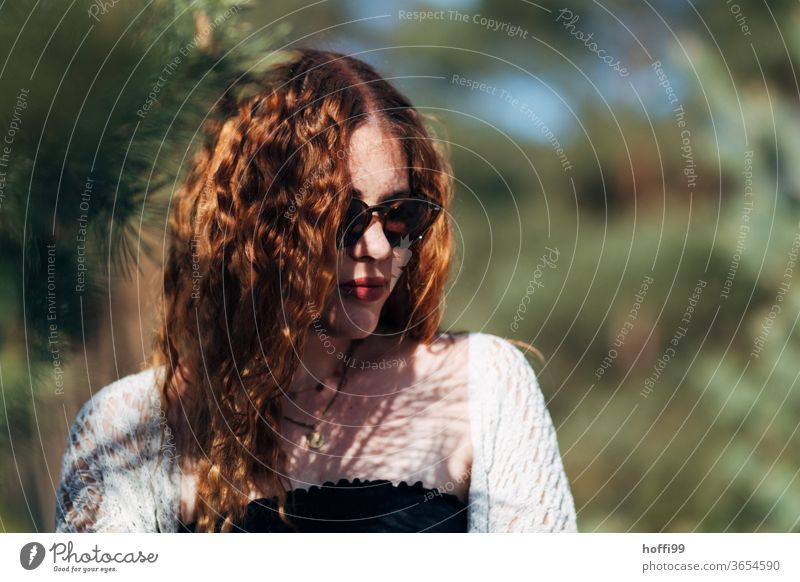 the young woman with sunglasses and red curly hair averts her eyes Woman red lips Sunglasses pretty Youth (Young adults) natural red hair Curly Lifestyle Lovely