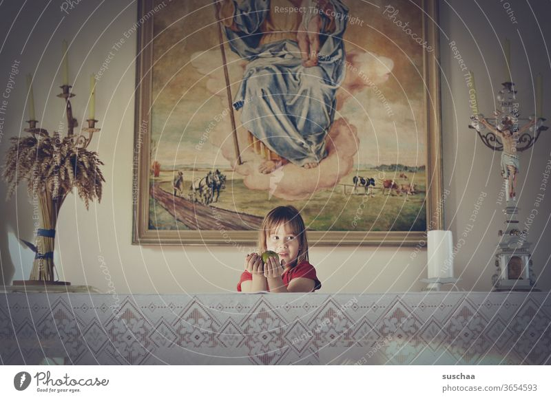 girl stands behind an altar in a chapel and holds an apple as a gift Chamansülz Holy Infancy Parenting tablecloth cross house of God Catholicism Candle holder