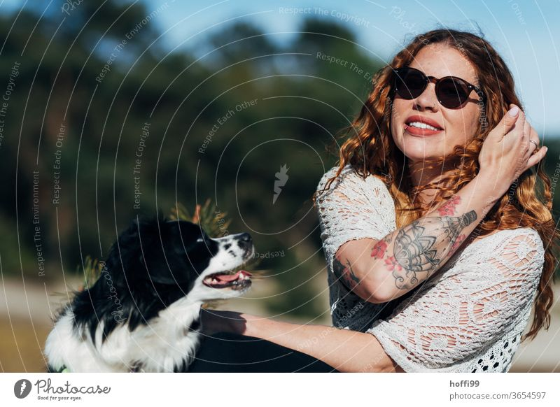 the young woman with sunglasses is enjoying the sun, Lana her dog wants to play... Woman red lips Sunglasses tattooing pretty Youth (Young adults) curly hair