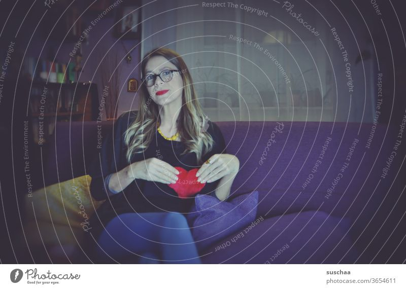 woman with red lips on a sofa holding a red fabric heart in front of her breast Woman Sofa Living room Lonely by oneself Love Loneliness Head Quarantine