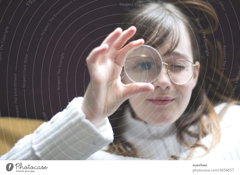 teenager holding a magnifying glass in front of her eyes Youth (Young adults) Face Eyeglasses hair Eyes Nose Mouth smile peep enlargement Magnifying glass